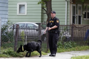 A Cuyahoga County Sheriff&#039;s deputy leads a dog through the neighborhood outside Ariel Castro&#039;s home in Cleveland