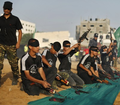 Blindfolded young Palestinians dismantle weapons during a military-style graduation ceremony at Fajer Al-Entesar summer camp, organised by the Hamas movement, in Gaza City
