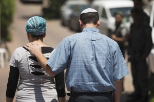 Bat-Galim and Ofir Shaer, parents of Gil-Ad, one of three missing teens, walk towards their home after addressing the media in Talmon