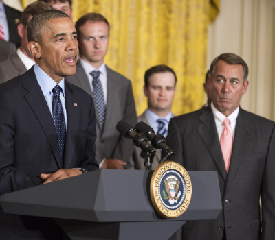 Boehner listens as Obama speaks during a ceremony honoring the President's Cup golf teams in Washington
