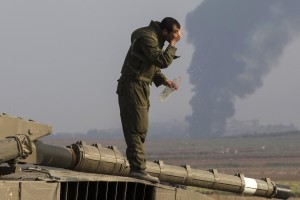 An Israeli soldier splashes water on his face as he stands atop  a tank outside the northern Gaza Strip