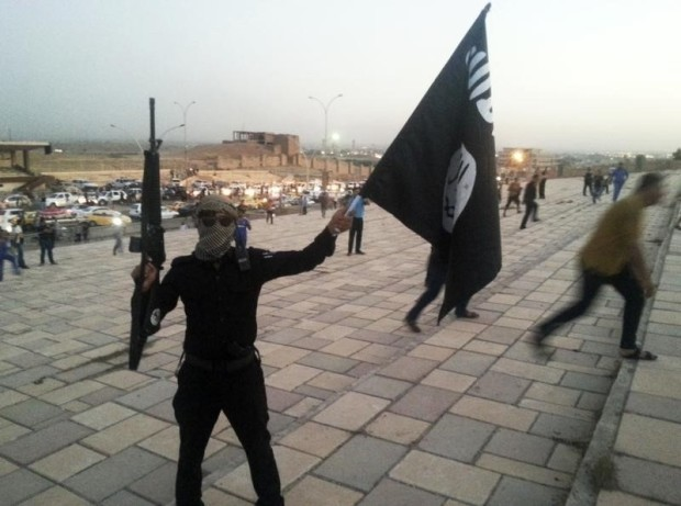 A fighter of the ISIL holds a flag and a weapon on a street in Mosul