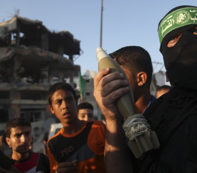 A Hamas militant displays a mortar shell as he celebrates what the militants say was a victory over Israel, in front of a destroyed house in the Shejaia neighborhood east of Gaza City