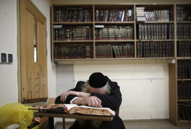 An Ultra-orthodox Jew leans on a religious Jewish text inside a Jerusalem synagogue