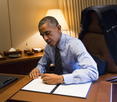 U.S. President Obama signs two Presidential Memoranda associated with his Executive Actions on immigration from his office on Air Force One upon his arrival in Las Vegas