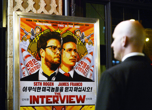 """A security guard stands at the entrance of United Artists theater during the premiere of the film """"The Interview"""" in Los Angeles"""