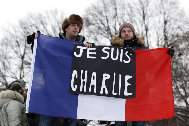 "Two men hold a sign reading ""I am Charlie"" and a French flag during a tribute for the victims of the Paris shootings, in Ottawa"