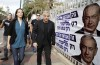 Yesh Atid leader Lapid and his wife Lihi walk past Likud election campaign posters as they walk to a polling station in Tel Aviv