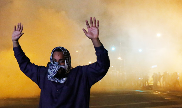 A protester raises his hands as clouds of smoke and crowd control agents rise shortly after the deadline for a city-wide curfew passed in Baltimore