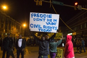 Residents, protesting the death of 25-year-old black man Freddie Gray, hold signs near riot police who lined the intersection of North Avenue and Pennsylvania Avenue ahead of a city-wide curfew in Baltimore, Maryland