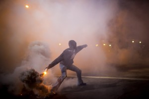 A protester throws a gas canister back at police during clashes at North Ave and Pennsylvania Ave in Baltimore, Maryland April 28, 2015.  REUTERS/Eric Thayer -