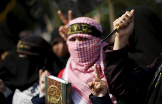 A Palestinian woman supporting the Islamic Jihad movement holds a copy of the Koran as another holds a knife during a rally in Gaza City to show solidarity with Palestinians confronting Israelis in the West Bank and Jerusalem October 20, 2015.  REUTERS/Mohammed Salem