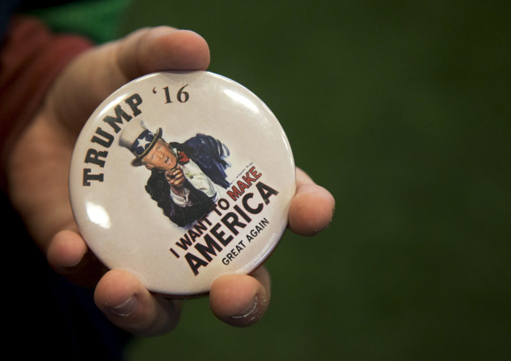 A man holds a button in support of Donald Trump at the Crete Civic Centre in Plattsburgh. REUTERS/Christinne Muschi