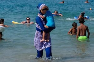 A woman wearing a burkini walks in the water August 27, 2016 on a beach in Marseille, France, the day after the country's highest administrative court suspended a ban on full-body burkini swimsuits that has outraged Muslims and opened divisions within the government, pending a definitive ruling.  REUTERS/Stringer