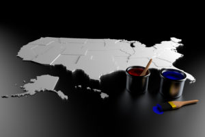A gray map of the United States on a black surface. A bucket of red paint and a bucket of blue paint with paintbrushes nearby.