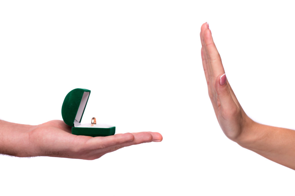 Marriage proposal rejection. Cropped image of an open ring box and woman hand refusing to accept it isolated on white background