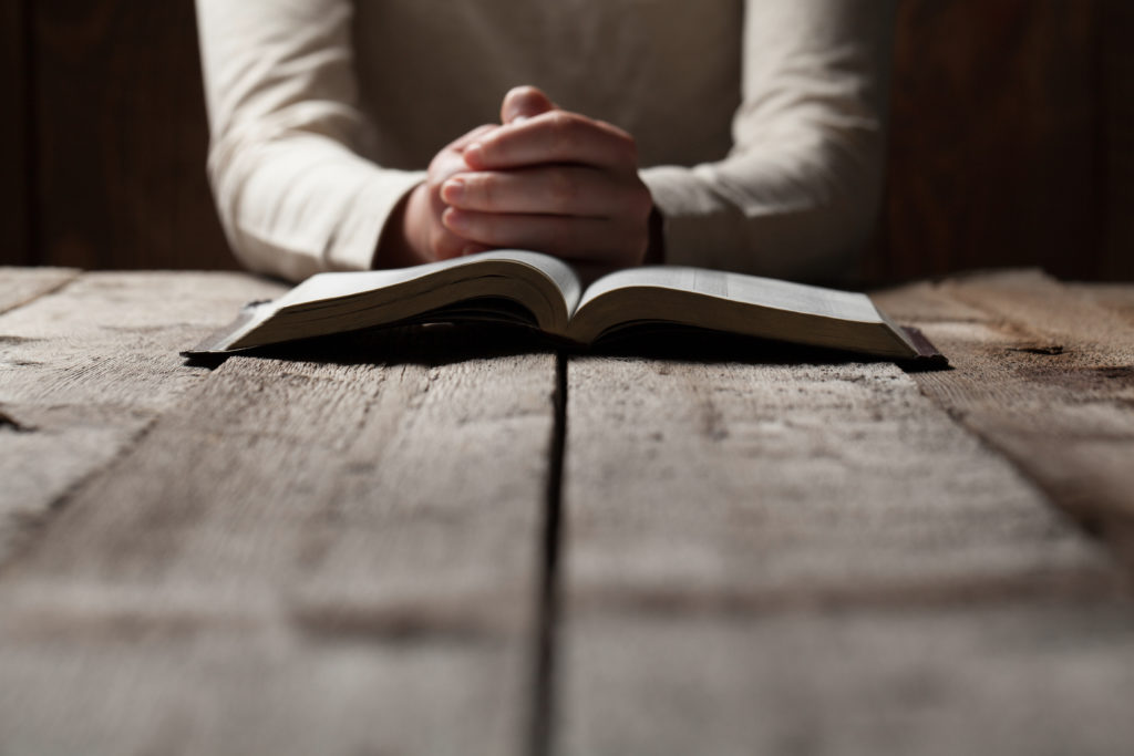 Woman hands praying with a bible in a dark over wooden table
