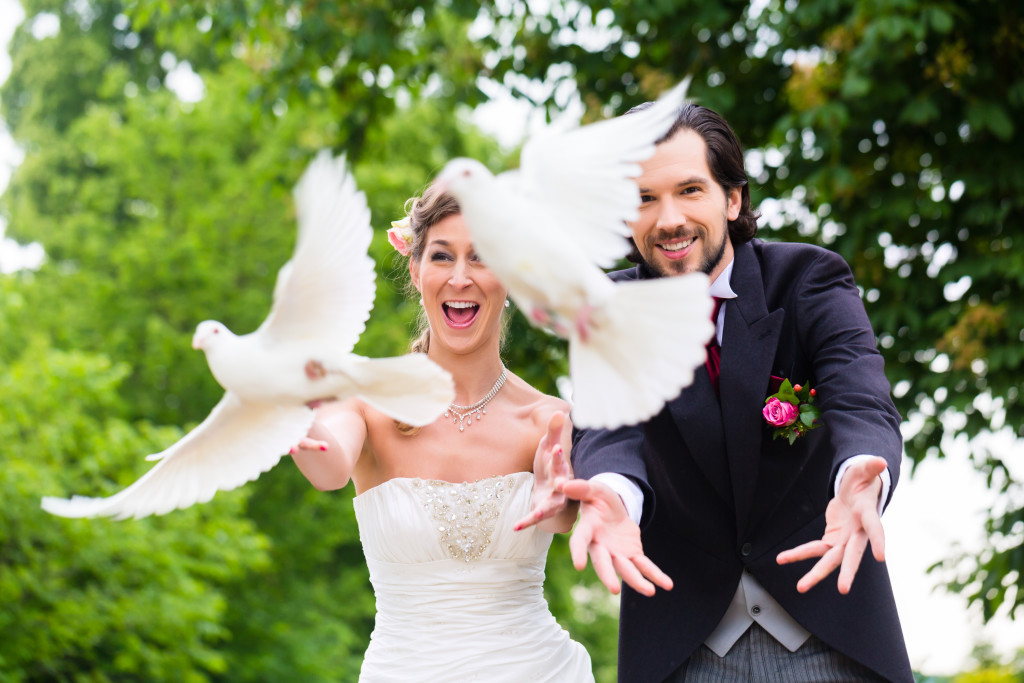 Bridal pair with flying white doves at wedding