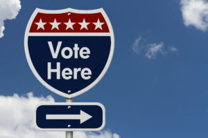 American Vote Here Highway Road Sign, Red, White and Blue American Highway Sign with words Vote Here with sky background