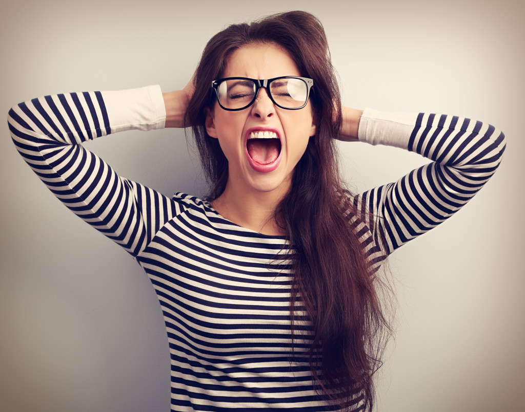 Angry young business woman in glasses strong screaming with wild open mouth and holding head the hands. Toned closeup portrait