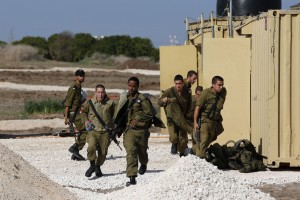 Israeli soldiers, stationed at an Iron Dome rocket shield battery site, run for cover as a siren is sounded warning of incoming rockets near Ashdod
