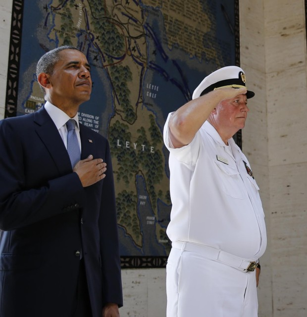 U.S. President Obama stands at attention during a wreath-laying ceremony at the Manila American Cemetery
