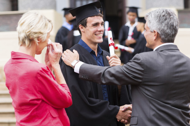 male graduate being congratulated by his father