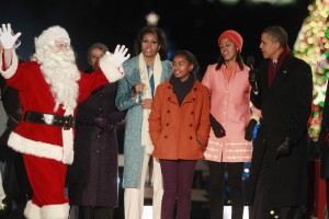 U.S. President Obama, first lady and their daughters sing alongside an actor dressed as Santa in Washington